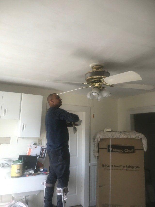 Man doing drywall repairs around ceiling fan